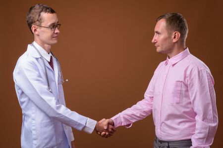 Young man doctor and man patient against brown background Stock Photo