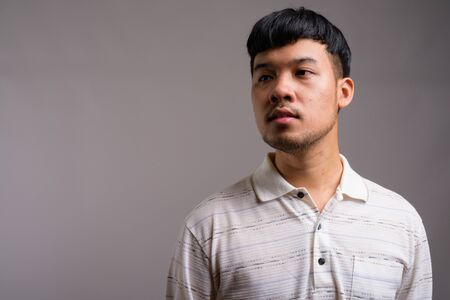 Portrait of young Asian man against gray background