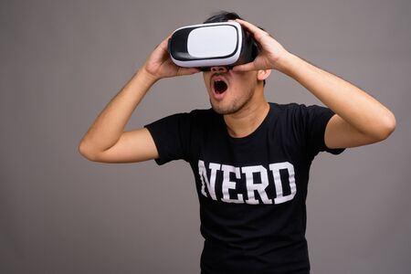 Young Asian nerd man using virtual reality headset