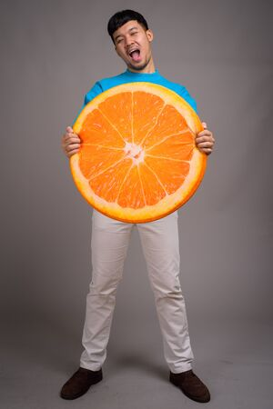 Portrait of young Asian man holding big slice of orange