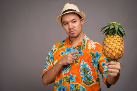 Portrait of young Asian tourist man holding pineapple Imagens