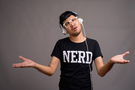 Young Asian nerd man listening to music against gray background