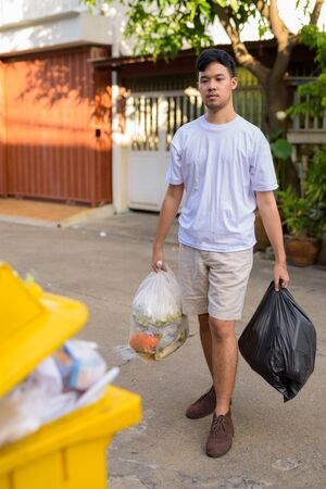 Young Asian man taking out the garbage at home