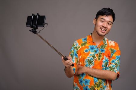 Young Asian tourist man ready for vacation against gray backgrou Imagens