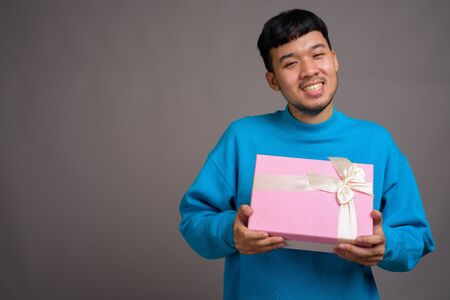 Portrait of young Asian man holding gift box