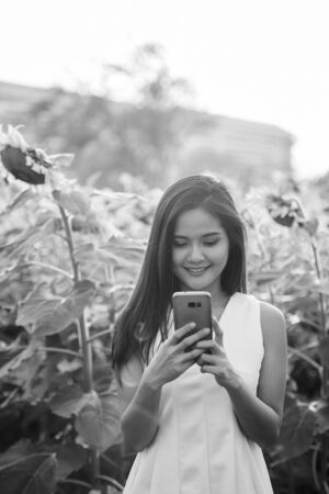 Young happy Asian woman smiling while using mobile phone in the field of blooming sunflowers