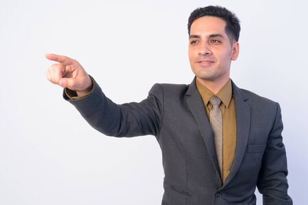 Portrait of happy Persian businessman in suit directing and pointing finger