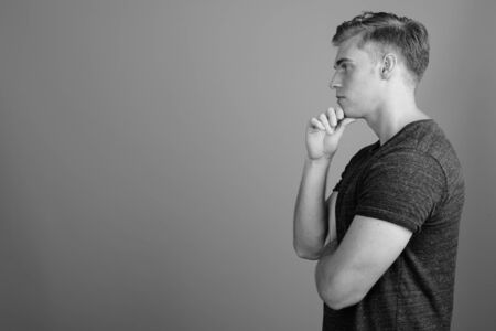 Profile view of young handsome man against gray background in black and white