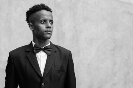 Giovane uomo d'affari africano bello che indossa tuta contro il muro di cemento all'aperto Archivio Fotografico