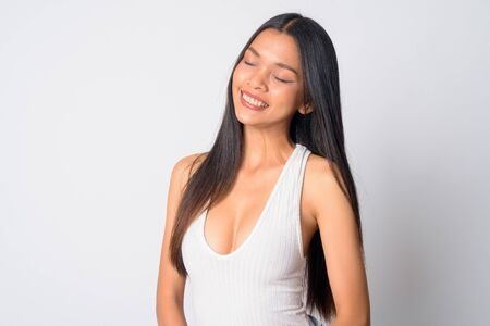 Portrait of happy young beautiful Asian woman relaxing with eyes closed
