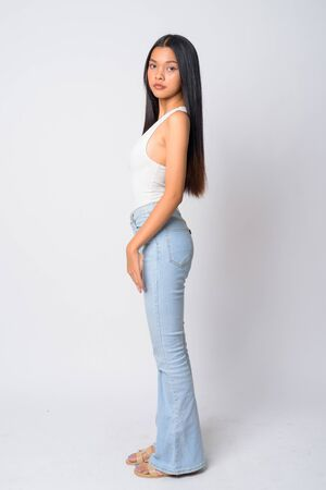Full body shot profile view of young beautiful Asian woman looking at camera Stok Fotoğraf