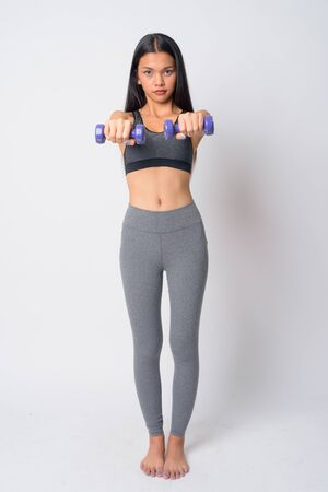Full body shot of young Asian woman exercising with dumbbells and ready for gym