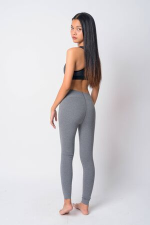 Full body shot rear view of young Asian woman looking over shoulder ready for gym
