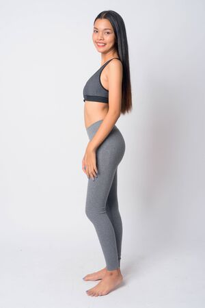 Full body shot profile view of happy young Asian woman ready for gym