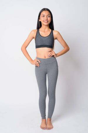 Full body shot of happy young Asian woman thinking ready for gym