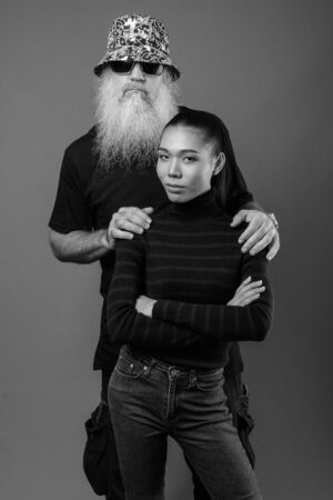 Mature bearded man with young Asian transgender woman together in black and white Фото со стока