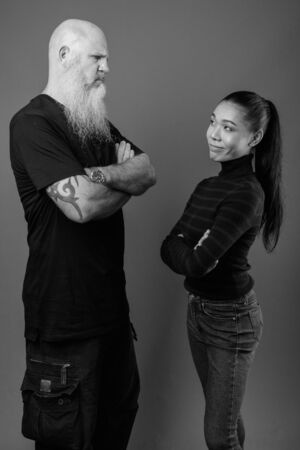 Mature bearded bald man with young Asian transgender woman together in black and white Фото со стока