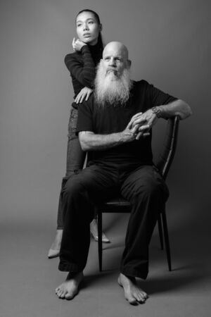 Mature bearded bald man with young Asian transgender woman together in black and white Reklamní fotografie