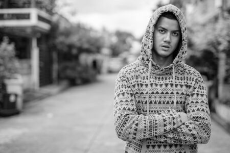 Young multi ethnic Asian man outdoors in black and white