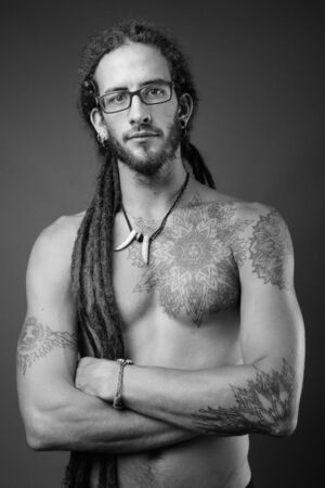Young handsome Hispanic man with dreadlocks shirtless in black and white Reklamní fotografie