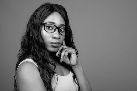 Young beautiful African woman wearing eyeglasses against gray background