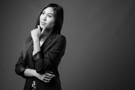 Young beautiful Asian businesswoman in black and white Stock Photo