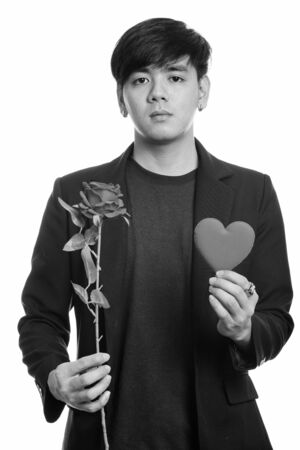 Studio shot of cool handsome Asian businessman holding red roses and heart