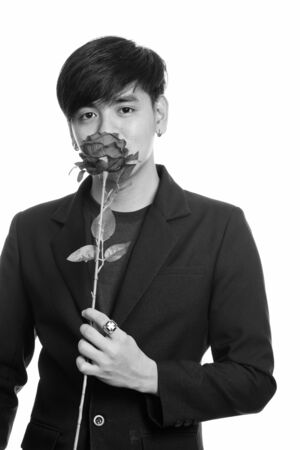 Studio shot of cool handsome Asian businessman smelling red roses