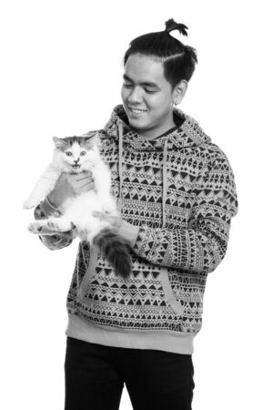 Studio shot of young happy Asian man smiling while holding cute cat Archivio Fotografico - 134400811