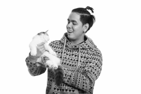 Studio shot of young happy Asian man smiling while holding cute cat Archivio Fotografico - 134400909