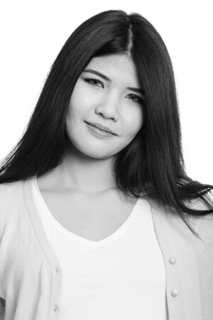 Face of young beautiful Asian woman in black and white