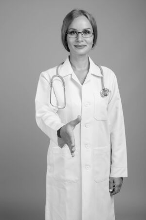 Young beautiful woman doctor with blond hair in black and white 스톡 콘텐츠
