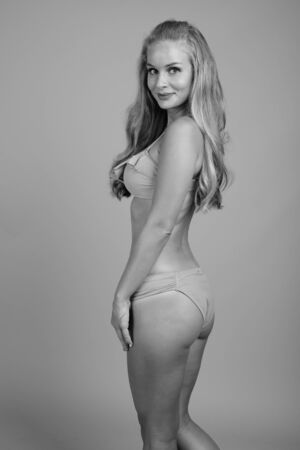 Young beautiful woman with blond hair wearing bikini in black and white