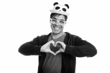Happy Persian man smiling and giving hand heart sign while wearing cute hat and yellow eyeglasses 스톡 콘텐츠