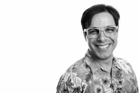 Studio shot of young happy Persian tourist man smiling while wearing eyeglasses isolated against white background
