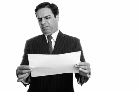 Studio shot of young Persian businessman reading on paper while looking disgusted isolated against white background