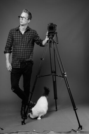 Young handsome hipster man vlogging with camera in black and white