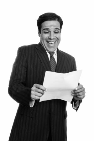 Studio shot of young happy Persian businessman smiling and laughing while reading on paper