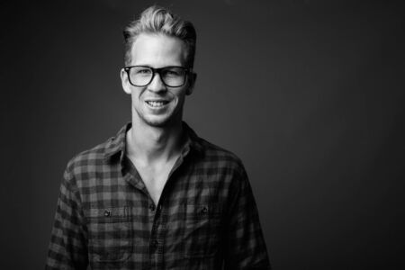 Studio shot of young handsome hipster man in black and white