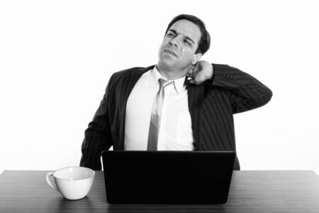 Studio shot of young Persian businessman thinking while having neck pain with laptop and coffee cup on wooden table