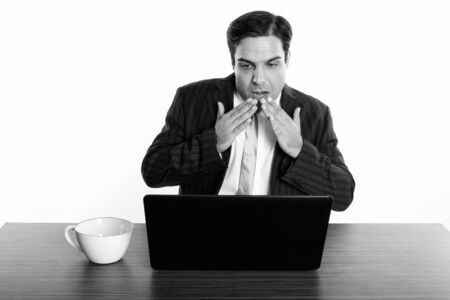 Studio shot of young Persian businessman looking shocked while using laptop with coffee cup on wooden table