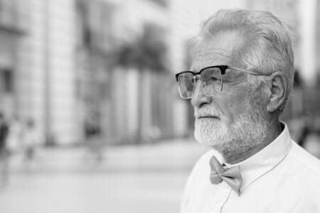 Przystojny brodaty starszy turysta mężczyzna zwiedzający miasto w czerni i bieli