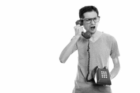 Studio shot of angry young man talking on old telephone Stock Photo