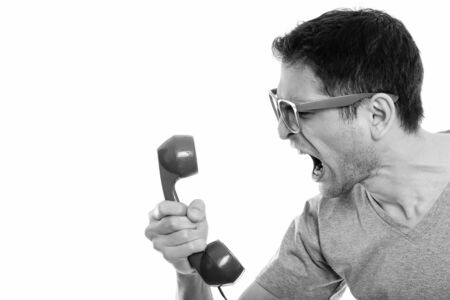 Close up of angry young man shouting at old telephone Stock Photo