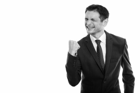 Studio shot of happy young businessman smiling while looking motivated with eyes closed Stock fotó