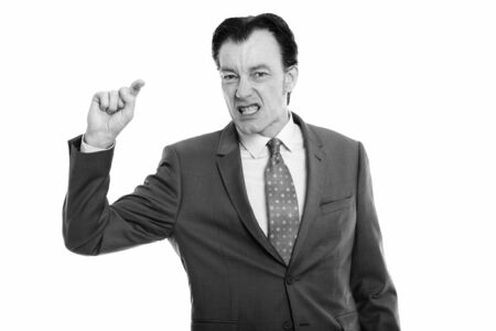 Studio shot of mature businessman looking furious while pointing finger