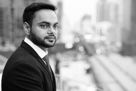 Młody brodaty indyjski biznesmen na tle miasta