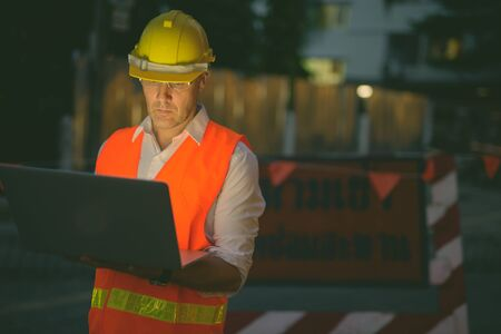 Mature man construction worker at the construction site in the city at night