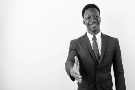 Young handsome African businessman wearing suit against white background