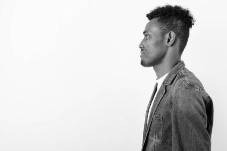Jonge, bebaarde Afrikaanse man met een spijkerjasje tegen een witte achtergrond Stockfoto